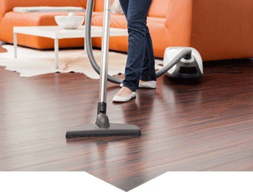 woman with vacuum cleaner cleaning the floor